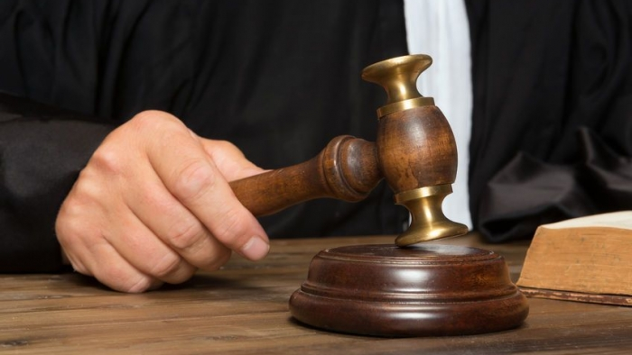 24568396 - hand of a judge holding a hammer or gavel